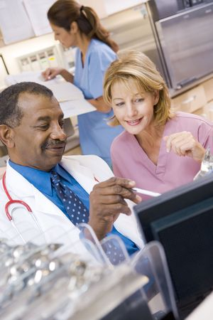 nurses station: A Doctor And Nurse Discussing Something At The Reception Area Of A Hospital