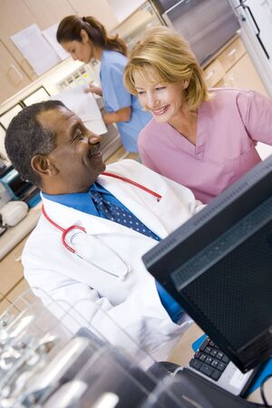 A Doctor And Nurse Discussing Something At The Reception Area Of A Hospital photo