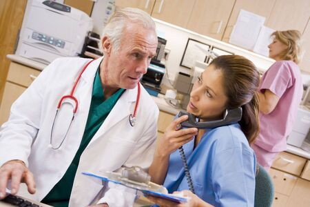nurses station: A Doctor And Nurse At The Reception Area Of A Hospital