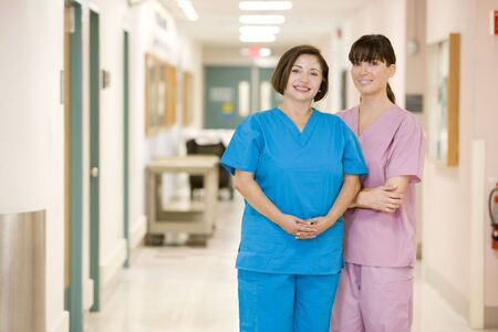 nursing young: Two Female Nurses Standing In A Hospital Corridor Stock Photo