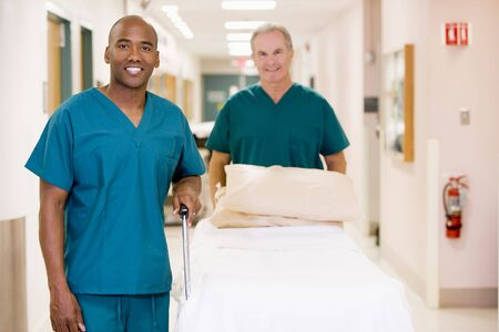 personal medico: Dos ordenanzas empujando una cama vac�a en un hospital del Corredor Foto de archivo