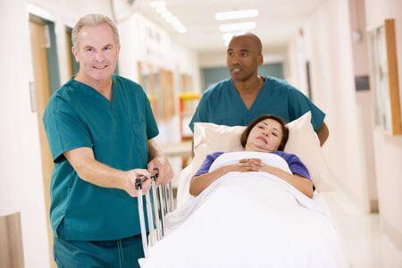 empujando: Dos ordenanzas empujando a una mujer en una cama de un hospital del Corredor