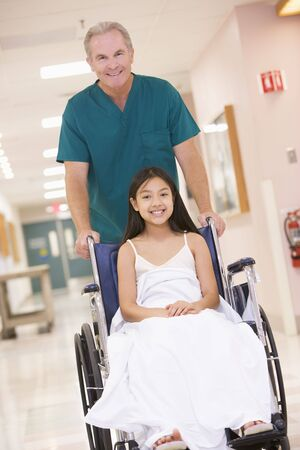 An Orderly Pushing A Little Girl In A Wheelchair Down A Hospital Corridor Stock Photo - 3723709