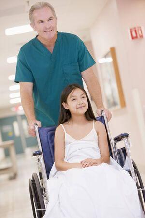 9 year old: An Orderly Pushing A Little Girl In A Wheelchair Down A Hospital Corridor Stock Photo