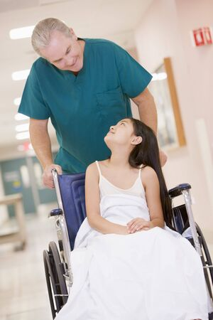 An Orderly Pushing A Little Girl In A Wheelchair Down A Hospital Corridor photo