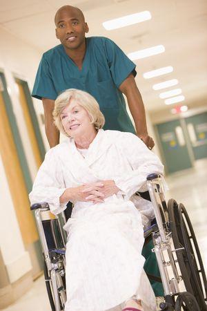 pushing: An Orderly Pushing A Senior Woman In A Wheelchair Down A Hospital Corridor Stock Photo