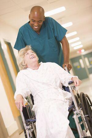 ordelijk: Een ordelijke Pushing Een hoge vrouw in een rolstoel Down Een Ziekenhuis Corridor