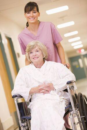 A Nurse Pushing A Senior Woman In A Wheelchair Down A Hospital Corridor Stock Photo - 3723939