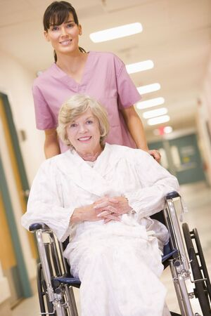 hospital corridor: A Nurse Pushing A Senior Woman In A Wheelchair Down A Hospital Corridor