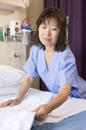mujer en la cama: Una enfermera toma una cama en un hospital Ward Foto de archivo