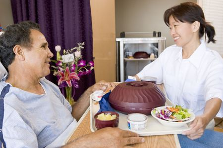 hospital background: Nurse Serving A Patient A Meal In His Bed Stock Photo