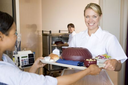 lunch tray: Nurse Serving A Patient A Meal In Her Bed