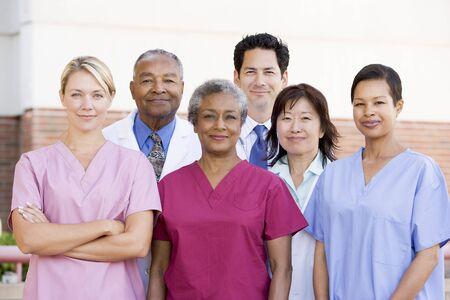 personal medico: El personal del hospital de pie fuera de un hospital