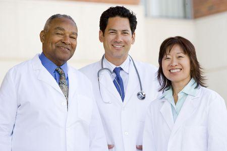 staff medico: Tre medici permanente al di fuori di un ospedale Archivio Fotografico