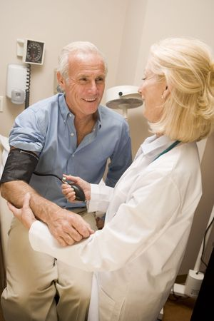 Doctor Checking Blood Pressure Of Man photo