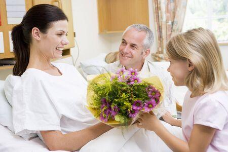 apoyo familiar: Ni�a de dar flores a su madre en el hospital Foto de archivo