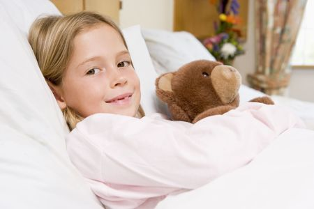 7 year old girl: Young Girl Lying In Hospital Bed,Holding Teddy Bear Stock Photo