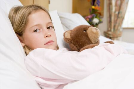 Young Girl Lying In Hospital Bed With Teddy Bear photo