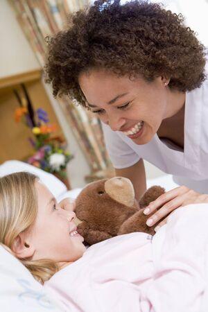 Nurse Laughing With Her Young Patient photo