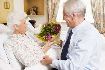 healthcare visitor: Senior Man Giving Flowers To His Wife In Hospital Stock Photo