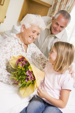 Granddaughter Giving Flowers To Her Grandmother In Hospital photo