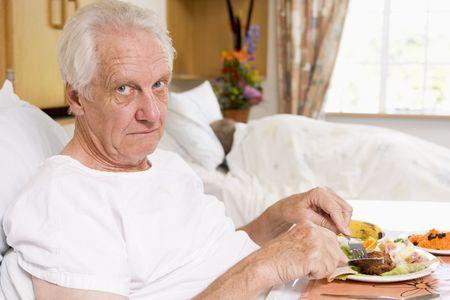 hombre comiendo: Superior hombre hospital comer alimentos en la cama Foto de archivo