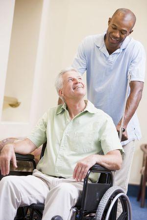 Nurse Pushing Man In Wheelchair Stock Photo - 3723822