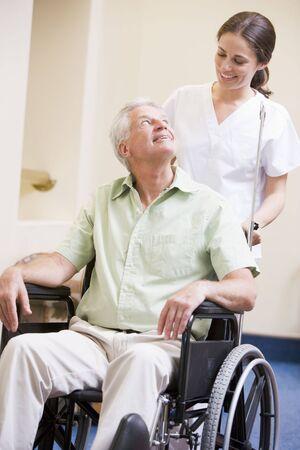 Nurse Pushing Man In Wheelchair Stock Photo - 3723840