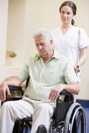Nurse Pushing Man In Wheelchair photo