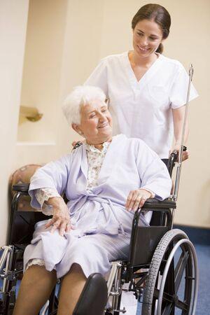 empujando: Enfermera empujando a la mujer en la silla de ruedas