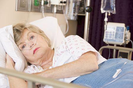 one senior adult woman: Superior de la mujer tumbado en la cama de hospital