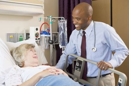 man doctor: Doctor Talking To Senior Woman Lying In Hospital Bed Stock Photo