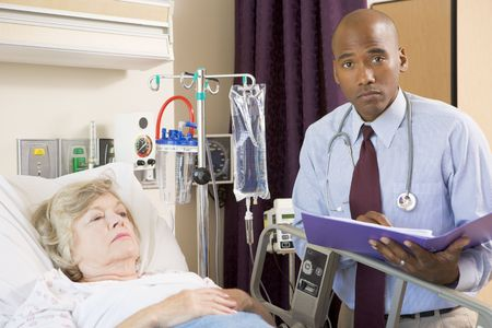 making notes: Doctor Making Notes About Patient,Looking Serious Stock Photo
