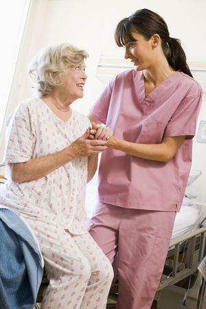 patient in bed: Nurse Helping Senior Woman To Walk Stock Photo