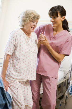 recovering: Nurse Helping Senior Woman To Walk Stock Photo