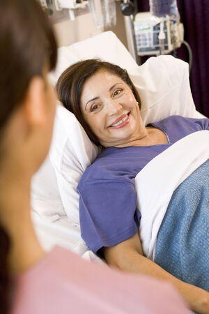 enfermera con paciente: Superior de la mujer tumbado en la cama de hospital, sonriendo