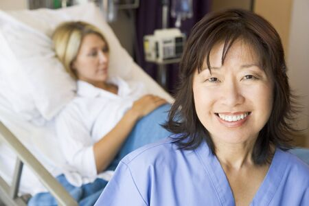 midwife: Doctor Standing In Patients Room,Smiling Stock Photo