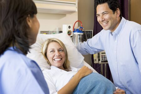 maternity ward: Doctor Talking To Pregnant Woman And Her Husband Stock Photo