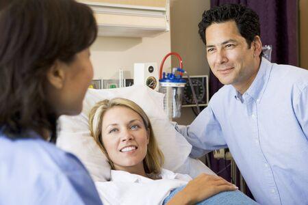 mujer en la cama: Doctor hablando con la mujer embarazada y su marido
