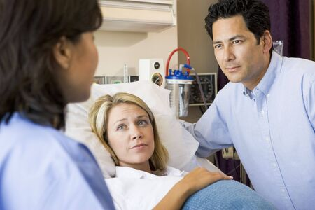 Doctor Talking To Pregnant Woman And Her Husband photo