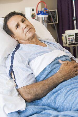 malade au lit: Homme couch� dans un lit d'h�pital Banque d'images