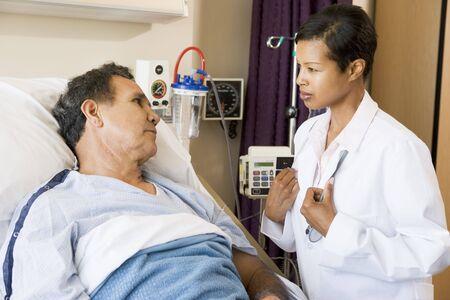 hombre preocupado: M�dico y paciente hablar el uno al otro Foto de archivo