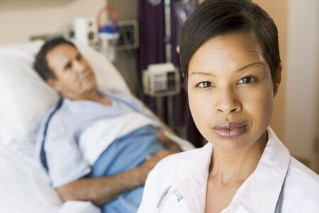 hospital bed: Doctor Looking Serious,Standing In Hospital Room Stock Photo
