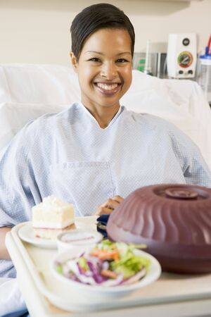 hospital bed: Woman Sitting In Hospital Bed With A Tray Of Food Stock Photo