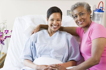 healthcare visitor: Mother And Daughter Smiling In Hospital Stock Photo
