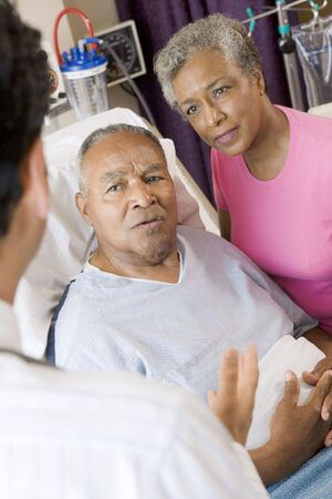 Senior Couple Talking To Doctor photo
