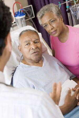 Senior Couple Talking To Doctor photo