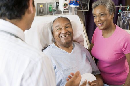 healthcare visitor: Senior Couple Talking,Smiling With Doctor Stock Photo
