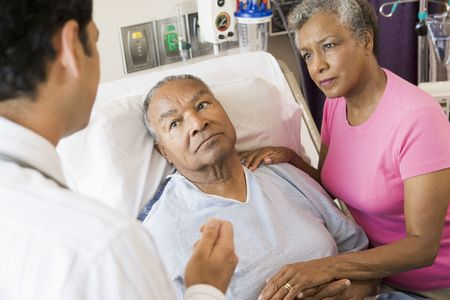 healthcare visitor: Senior Couple Talking To Doctor,Looking Worried