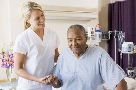 personas ayudandose: Ayudar a la enfermera superior de hombre a caminar
